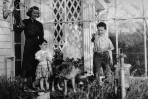 ca. 1940s, California, USA --- J. Robert Oppenheimer's wife, Katherine, stands next to daughter, Katherine, and overlooks an atrium where son, Peter, points something of interest out. --- Image by © CORBIS